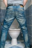 Man peeing to toilet bowl in restroom from back Stock Image
