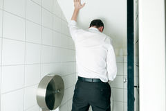 Man peeing in toilet. In a nightclub Stock Photo