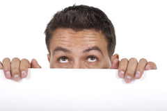 Man peeking behind empty white billboard Royalty Free Stock Photos