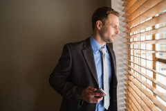 Man peeking through blinds while holding his phone Stock Images