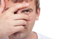 Man peeking through fingers Stock Photo