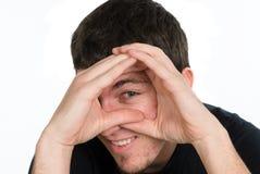 Man peeking through hands Royalty Free Stock Photos