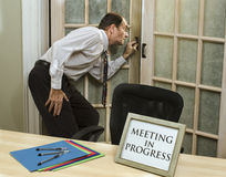 Man peeking into meeting in progress Royalty Free Stock Image