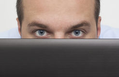 Man peeking over laptop Stock Image