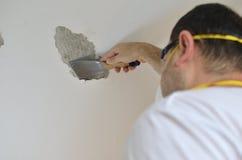 Man Peeling a Ceiling Stock Image