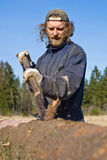 Man peeling logs stock photography