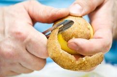 Man peeling a potato Royalty Free Stock Image