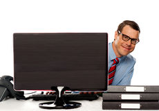 Man peeping from behind computer screen Stock Images