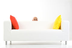 Man peeping from behind sofa Royalty Free Stock Photos