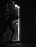 Man peeping through the door at night Stock Photo