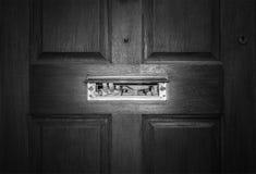 Man peeping through letterbox Stock Photo