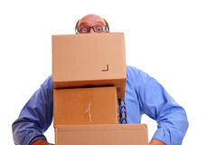 Man peeps over heavy boxes while carrying them Royalty Free Stock Images
