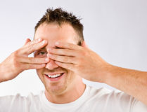 Man peering from behind hands Stock Images