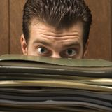 Man peering from behind pile of folders. Royalty Free Stock Images