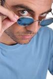 Man peering over his sunglasses stock photos