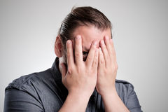 Man peers through his fingers. He hesitates to show his face Stock Photography