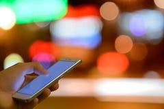 Man pekskärmmobiltelefonen, ljus bokehbakgrund för natt Arkivbild