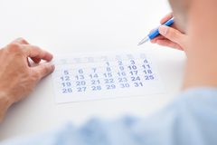 Man with pen looking at calendar Royalty Free Stock Images
