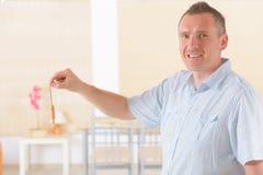Man with pendulum. Man dowser using wooden pendulum, tool for dowsing Stock Photography