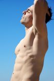 Man with perfect body with closed eyes in front of sky Stock Photography