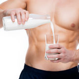 Man with perfect body pouring milk into a glass. Royalty Free Stock Image
