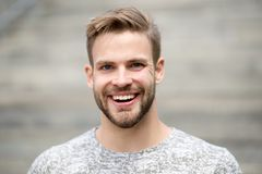 Man with perfect brilliant smile unshaven face defocused background. Guy happy emotional expression outdoors. Bearded
