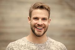 Man with perfect brilliant smile unshaven face defocused background. Guy happy emotional expression outdoors. Bearded stock photography