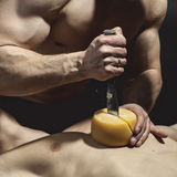 Man with a perfect figure sliced cheese on the body of another a Royalty Free Stock Photos