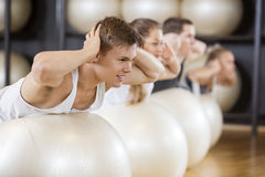 Man Performing Back Extension Exercise With Friends On Balls Stock Photos