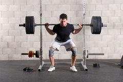 Man performing a crossfit back squat exercise. Slowly raising himself from the squatting to uoright position with a heavy barbell weight on his shoulders stock images