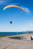 Man performing flyby over woman with yellow and blue parasail. Man riding yellow and blue parasail over woman looking up Royalty Free Stock Photos
