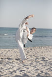 Man performing a high kick on the beach Stock Images