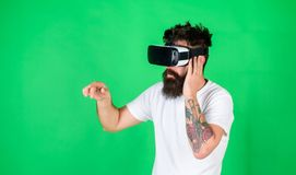 Man performing musical show in virtual reality simulation game. Bearded man with tattoo wearing VR headset. Man with. Hipster beard using digital touch screen royalty free stock images