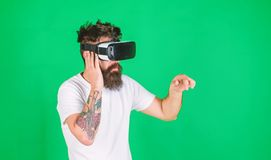 Man performing musical show in virtual reality simulation game. Bearded man with tattoo wearing VR headset. Man with. Hipster beard using digital touch screen stock image