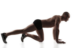 Man performing push-ups exercise. Silhouette of young man performing push-ups exercise, on white background Stock Photo