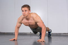 Man performing push ups at the gym Stock Images