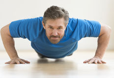 Man Performing Push-Ups On Floor At Home Royalty Free Stock Photos
