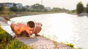 Man performing push ups by the river Stock Photo