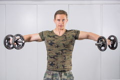 Man performing shoulder workout at the gym. Man performing shoulders workout at the gym Royalty Free Stock Images