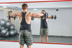 Man performing shoulder workout at the gym. Man performing shoulders workout at the gym Royalty Free Stock Photography