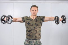 Man performing shoulder workout at the gym Stock Image