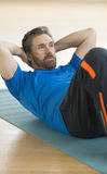 Man Performing Sit-Ups On Exercise Mat Royalty Free Stock Photos