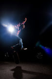 Man Performing Skateboarding Tricks. A young skateboarder doing jumping and kick flip tricks under dramatic rim lighting with lens flare Stock Photo