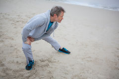 Man performing stretching exercise on beach royalty free stock images