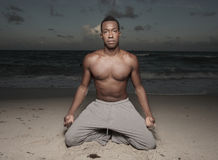 Man performing yoga on the beach. Attractive young man performing yoga on the beach during dusk Royalty Free Stock Photography