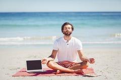 Man performing yoga at beach Stock Photography