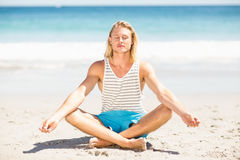 Man performing yoga at beach Stock Photo