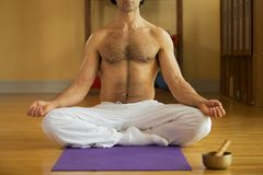 Man Performing Yoga in the lotus pose Stock Photo