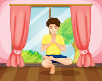 A man performing yoga near the window Stock Image