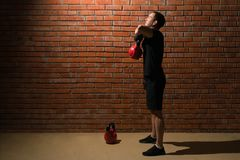 Man performs an exercise with a red dumbbell on a brick wall background royalty free stock images